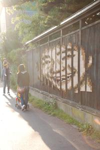 内野の商店街の黒塀に現れた「人の顔」
