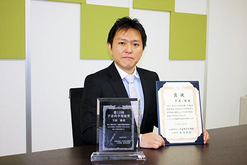 第12回宇宙科学奨励賞(宇宙理学分野)の賞状を掲げる超域学術院の下西隆助教