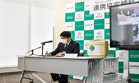 協定書にサインをする 鈴木一史 新潟大学日本酒学センター長
